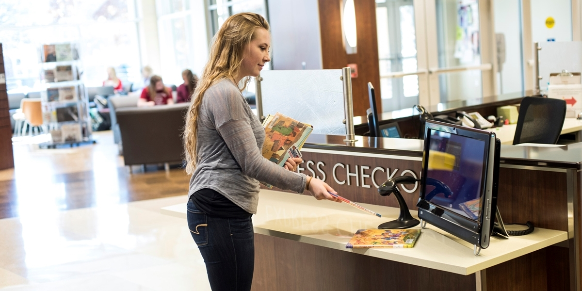 student checking out books at the Express Checkout station